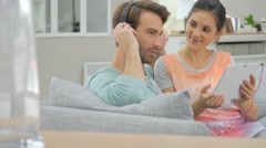 Couple sitting in sofa and websurfing on digital tablet Stock Footage