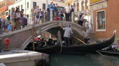 Tourists walking on a bridge and gondoliers paddling gondolas under it, Venice Stock Footage