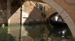 Man paddling a gondola under two bridges in Venice - stock footage