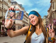 Happy traveler woman is taking selfie - stock photo
