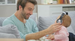 Daddy having baby girl listening to music with headphones Stock Footage