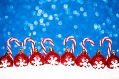 christmas red balls in snow on blue glitter background - stock photo