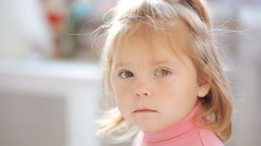 Blue-eyed blonde little girl looking bored and serious Stock Footage