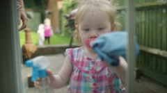 4K Cute little girl with cleaning cloth cleaning window from outside Stock Footage