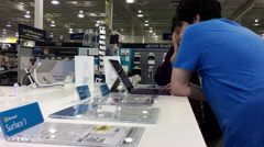 People trying new laptop inside Best buy store Stock Footage
