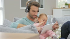 Daddy and baby girl in sofa using tablet and headphones - stock footage