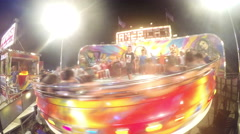 People enjoy spinning entertainment ride at night in luna park Stock Footage