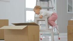 Baby girl trying to climb on scale Stock Footage