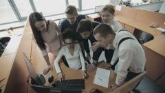 Group of multiethnic office workers around colleague using computer - stock footage