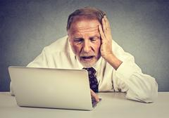 Portrait senior stressed man working on laptop sitting at table isolated on g Stock Photos