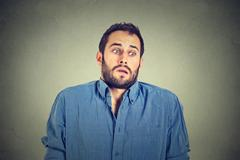 handsome man shrugging shoulders showing ignorance - stock photo