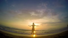 Happy girl running on the beach against sunset reflection and jumps in the wa Stock Footage