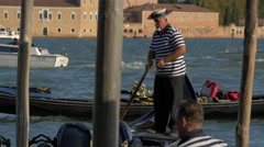 Old man with striped shirt and hat paddling a gondola in Venice Stock Footage