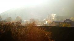 Houses, smoke, sun, mountains in fog, idyllic landscape Stock Footage