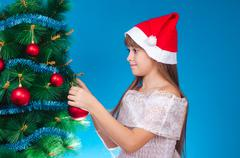 Stock Photo of The girl hangs up a toy on a fir-tree