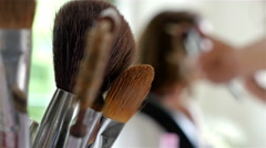 Make-up artist doing make-up of a model, make-up brushes on the front. Stock Footage