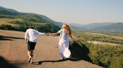Active hiking couple outdoors in mountains during hike. Young couple on trail Stock Footage