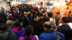 Asian people slowly rush through crowded market street aisle, overhead shot Stock Footage
