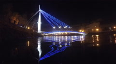 Bridge with lights reflected in the water at night Stock Footage
