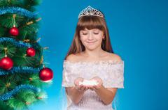 The girl with long hair in a red cap costs near a New Year tree and holds in - stock photo