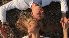 Happy bride and groom embracing lying on the ground - stock footage