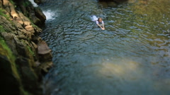 Beautiful woman enjoying bathing near natural waterfall slow motion Stock Footage