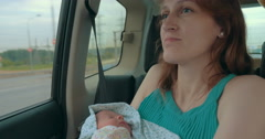 Young Mother Holding Newborn In The Car - stock footage