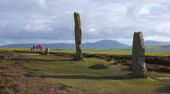 People walk near the sacred Celtic stones on the Islands of Orkney in Northern Stock Footage
