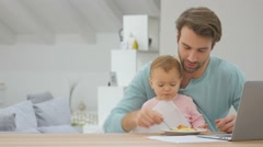 Man working from home and feeding baby Stock Footage