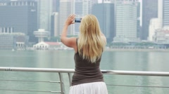 Woman taking picture of singapore city skyline and selfie Stock Footage