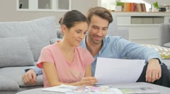 Couple looking at construction plan of future house Stock Footage