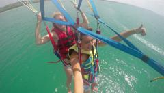 Happy Paraglider tandem flying over sea water Stock Footage