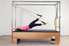 Pilates aerobic instructor woman in cadillac fitness exercise - stock photo