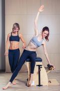 Combo wunda pilates chair woman with instructor fitness yoga gym exercise Kuvituskuvat
