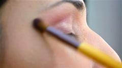 Make-up artist applying eyelash makeup to model's eye. Close up view - stock footage