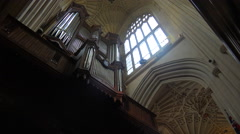 Interior of an old English church featuring a large pipe organ. - stock footage