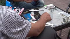 People gambling paper mahjong beside the road,sichuan Stock Footage