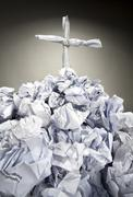 Grave with cross made of crumpled papers Stock Photos