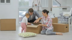 Stock Video Footage of Young family moving into new home, unpacking