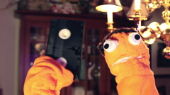 comedic puppet holding VHS tape cassette - stock footage