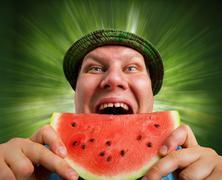 Stock Photo of Bizarre man eating watermelon