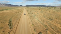 Aerial reverse track of vehicle (car) traveling off-road in outback Stock Footage