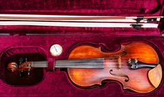 Top view of old violin with bow in red velvet case Stock Photos