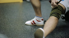 Male athletes aged rewinds his knee on the leg hair sport athletic bandage black Stock Footage