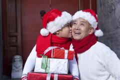 Grandpa and grandson holding Christmas Gifts - stock photo