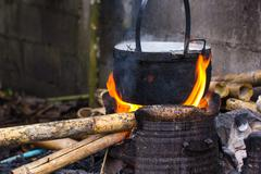 Close up of cooking in cauldron licked by flames on open fire fireplace made Stock Photos