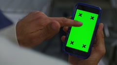 4K Close up of hand using a smartphone with green screen display Stock Footage