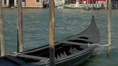 Black gondola moored to a mooring post in Venice Stock Footage