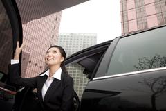 Businesswoman exiting a car - stock photo