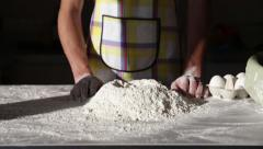 Man hands pour the flour and add egg Stock Footage
